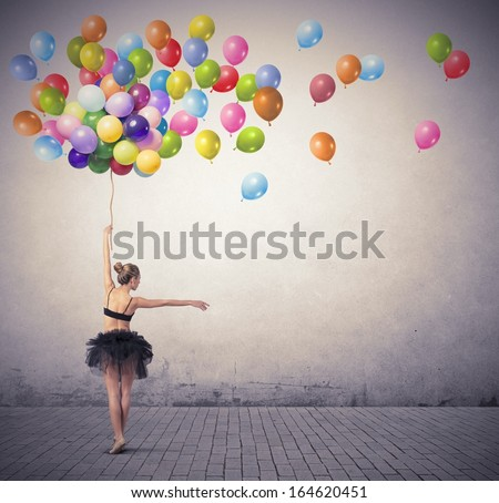 A beautiful girl dancing with colorful balloon - stock photo