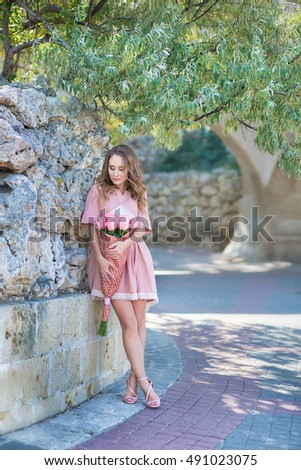A beautiful girl in a pink dress with a bouquet of large pink roses.  A girl in a pink dress with long beautiful legs