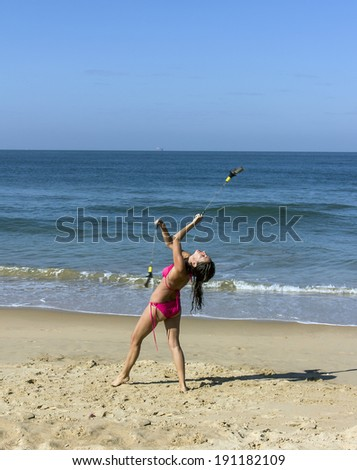 A beautiful girl in a red bikini is performing a poi dance at the beach of Goa