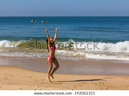 a beautiful girl in a red bikini is performing a poi-dance at the beach of Goa