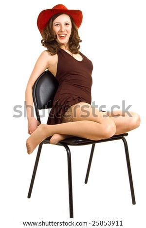 A beautiful girl in a red hat and brown dress sits on a chair. Isolation on a white background. - stock photo