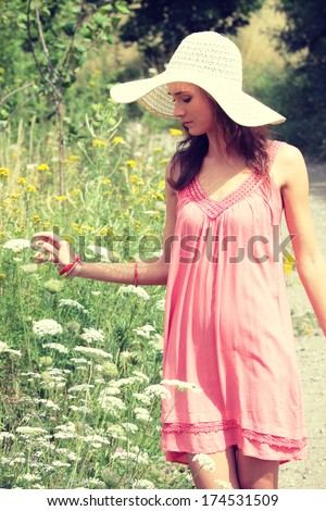a beautiful girl in big summer hat in the country  - stock photo