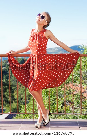 A beautiful girl in stylish dress having fun on the balcony of the hotel - stock photo