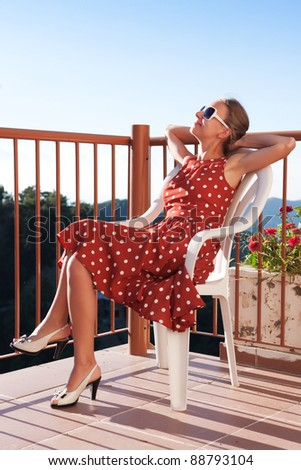 A beautiful girl in stylish dress resting on the balcony of the hotel