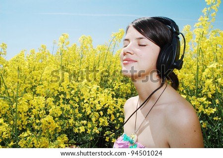 A beautiful girl listening music on a field of spring canola flowers. - stock photo