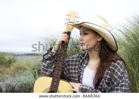 A beautiful girl posing with a guitar at the beach - stock photo