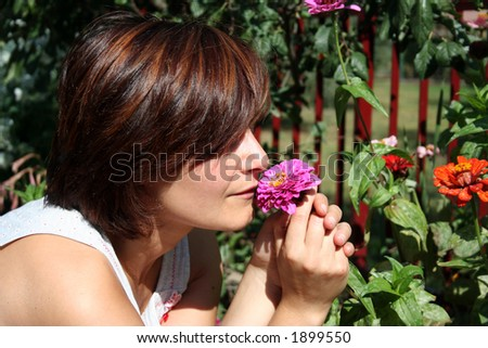 A beautiful girl smells the blossom odour of a colourful flower - stock photo