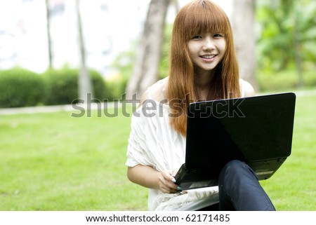 a beautiful girl using laptop at outdoor