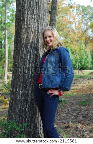 A beautiful girl wearing jeans and a blue denim jacket.  She's also wearing a red shirt and a red necklace.