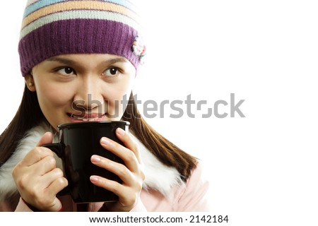 A beautiful girl wearing winter dress holding a cup of hot drink - stock photo