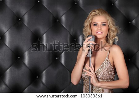 A beautiful girl with a microphone on stage singing a song - stock photo