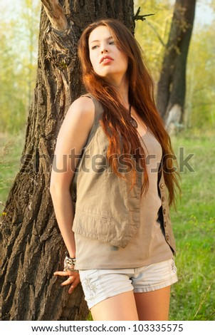 A beautiful girl with long hair outdoors - stock photo