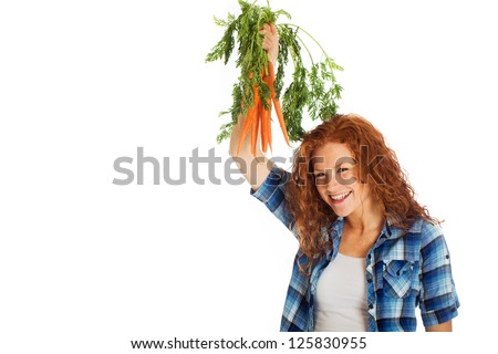 A beautiful girl with red hair proudly displaying her farm fresh carrots. - stock photo