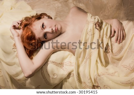 A beautiful girl with red hair resting in bed