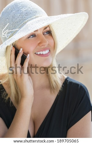 A beautiful girl young female woman with blond hair & blue eyes talking on her cell phone wearing white sun hat and little black dress - stock photo