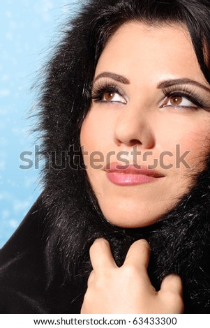 A beautiful glamorous brunette woman wearing makeup and a fashionable fur coat.  Blue background - stock photo