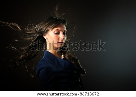 A beautiful glamorous woman in front of a black background with her hair blowing in the wind. - stock photo