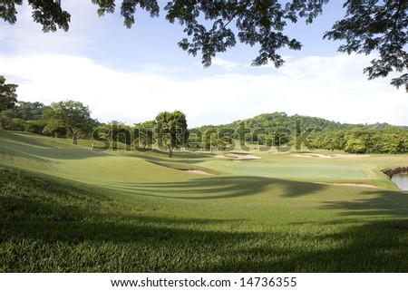 A beautiful golf course in lush tropical setting - stock photo