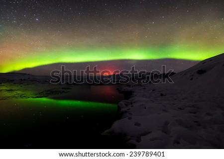A beautiful green and red aurora dancing over the Jokulsarlon lagoon, Iceland - stock photo