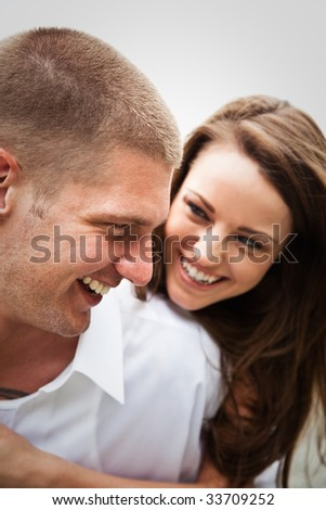 A beautiful happy caucasian couple in love on the beach - stock photo