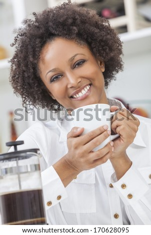 A beautiful happy mixed race African American girl or young woman drinking cafetiere coffee in her kitchen at home - stock photo