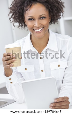 A beautiful happy mixed race African American girl or young woman using a tablet computer in her kitchen drinking coffee - stock photo