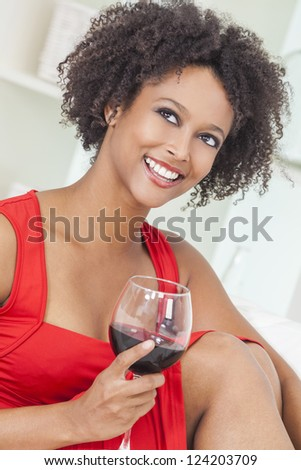 A beautiful happy mixed race African American girl or young woman wearing a red dress and drinking red wine at home - stock photo