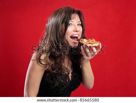 A beautiful happy woman eating a slice of tasty italian pizza. - stock photo