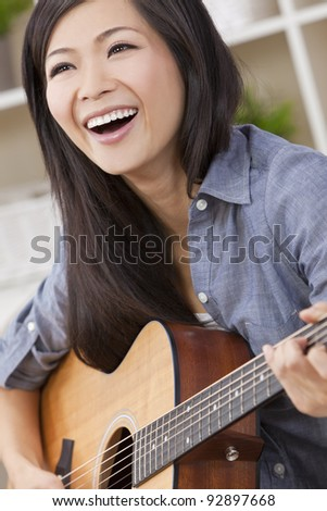 A beautiful happy young Chinese Asian Oriental woman with a wonderful toothy smile holding her guitar - stock photo