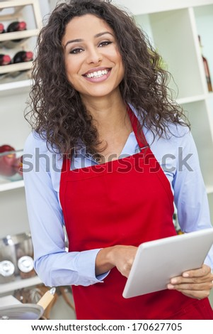 A beautiful happy young woman or girl wearing a red apron & using a tablet computer while cooking in her kitchen at home - stock photo