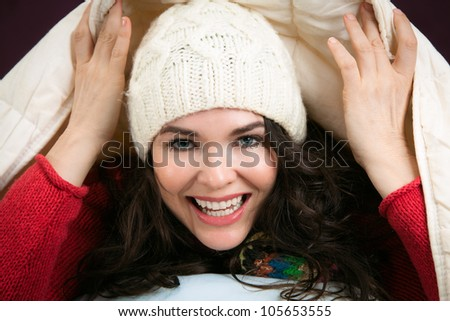 A beautiful happy young woman peeking out from underneath the blankets of her bed - stock photo