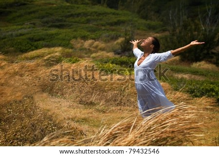 A beautiful Hawaiian woman stands in a meadow surrounded by wind-blown grass, dressed in white with hands and face raised to the sky. - stock photo