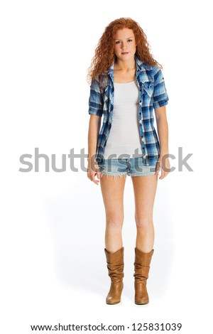 A beautiful, healthy girl with red hair wearing boots and short denim shorts. - stock photo