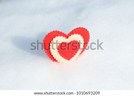 A beautiful heart made of cloth in the snow. Valentine's Day. Background.