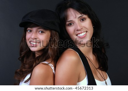 a beautiful hispanic mother and daughter sit back to back and smile before a black background. - stock photo