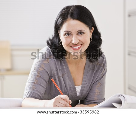A beautiful Hispanic woman writing at a desk.  She is smiling at the camera.  Square compostion. - stock photo