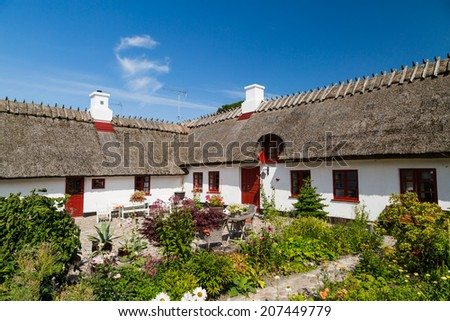 A beautiful historical white farm house with a thatched roof. - stock photo