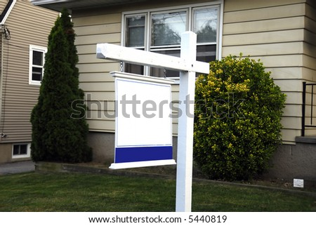 A beautiful house with a signboard for sale - stock photo