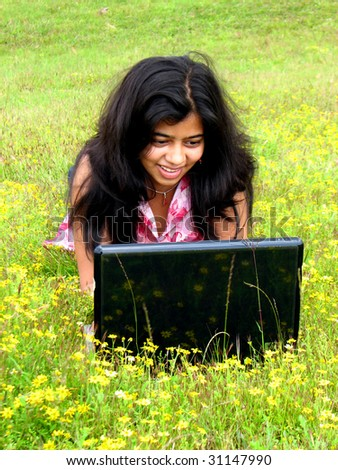 A beautiful Indian teenager using a laptop with wireless internet in the outdoors.