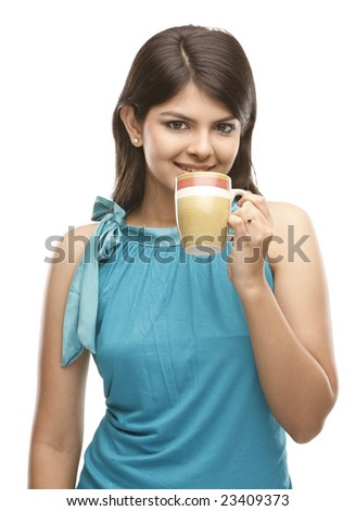 A beautiful indian young woman holding a cup - stock photo