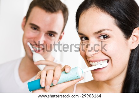 A beautiful interracial couple in the bathroom brushing teeth - stock photo