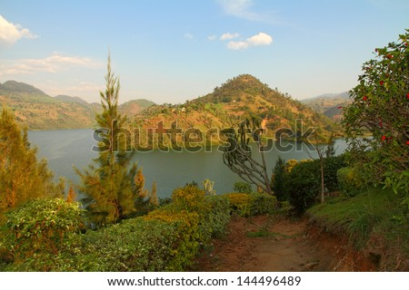 A beautiful lake and scenic hills scene from a garden path - stock photo