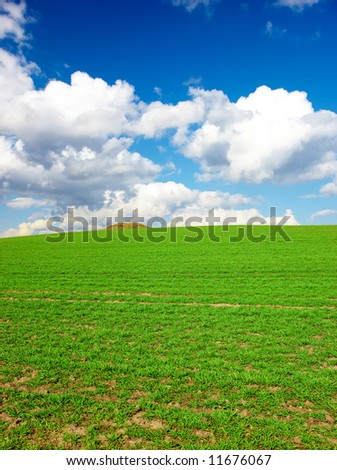 A beautiful landscape photo - springtime in the countryside with blue sky and green grass - stock photo