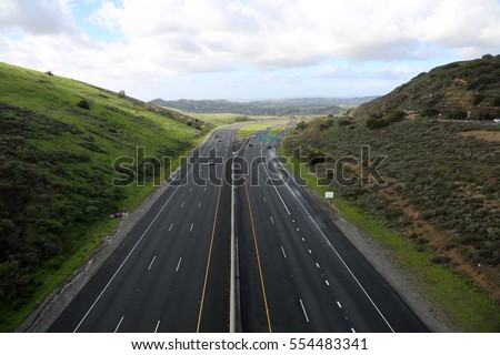 a beautiful 6 lane highway on a toll road in Orange County California with cars and green valley walls on both sides