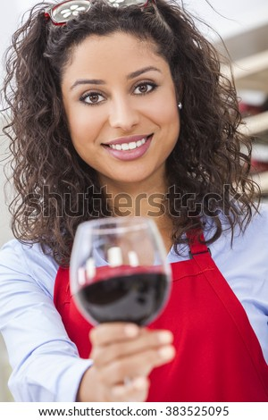 A beautiful latina hispanic girl or young woman drinking red wine at home toasting to camera - stock photo
