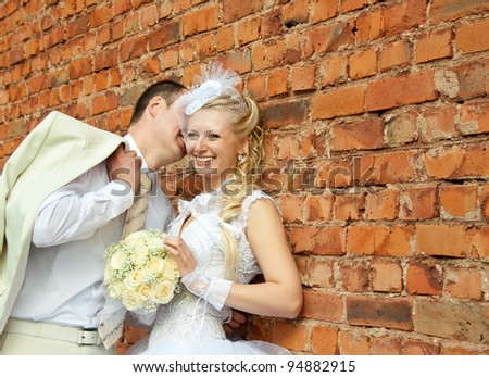 A beautiful laughing bride and a slender groom speak near the wall; wedding day - stock photo