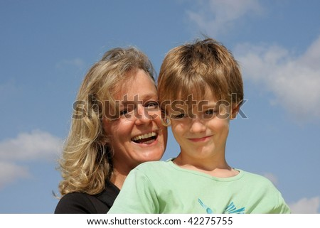 a beautiful laughing mother with her smiling 7-years old son photographed in the summer sun with blue sky and clouds in the background