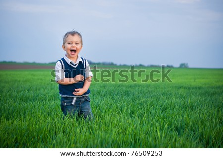 A beautiful little baby boy staing in the grass - stock photo