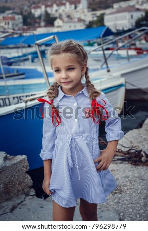 A beautiful little girl in a marine style against the backdrop of boats and yachts. Little Seaman