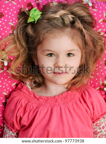 A beautiful little girl reclines on a pink pillow. - stock photo